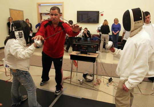 Minh Farrow dueled with Shaun Coughlan as instructor Cesar Morales adjusted their starting point during the Carroll Center for the Blind fencing tournament yesterday.