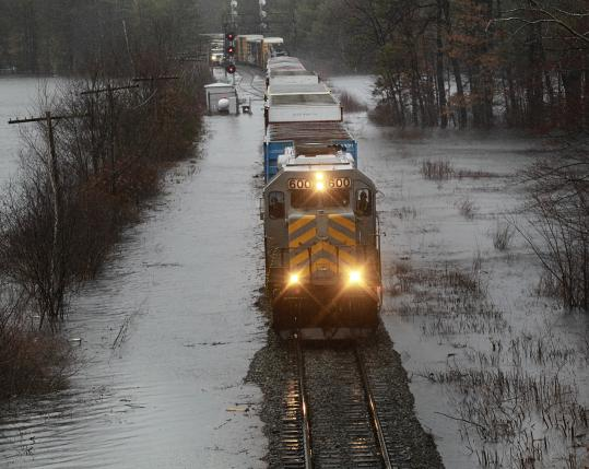 A train made slow progress along flooded tracks next to rain-swollen Spectacle Pond in Littleton yesterday.