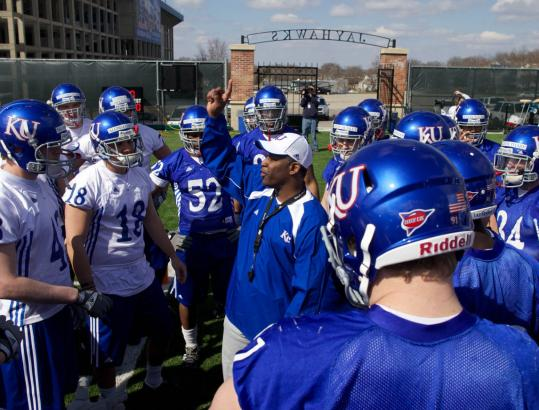 """Kansas football coach Turner Gill talks to his players during a spring practice last week. """"Equity seat rights'' are being pitched as a win-win for diehard fans and teams."""