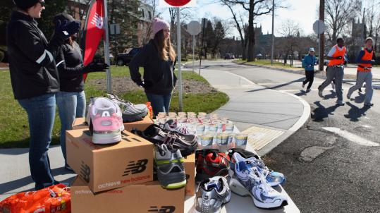 New Balance employees Kelly Gray, Cristen Murray, and Courtney English cheered on runners training for the Boston Marathon near Heartbreak Hill in Newton last week. New Balance will unveil limited-edition shoes for the race and hand out goodie bags and guides mapping out the course.