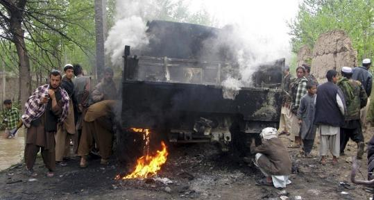 Taliban insurgents and civilians stood in front of a burning German military vehicle in Isaa Khail village in Kunduz Province. Three German soldiers were killed and five others wounded.