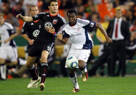 Kenny Mansally of the Revolution (right) charges upfield against Dejan Jakovic of D.C. United.