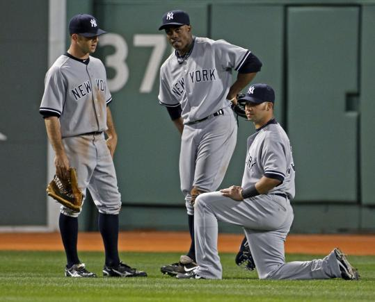 The Yankees outfield talks things over during a pitching change as the Red Sox storm back.