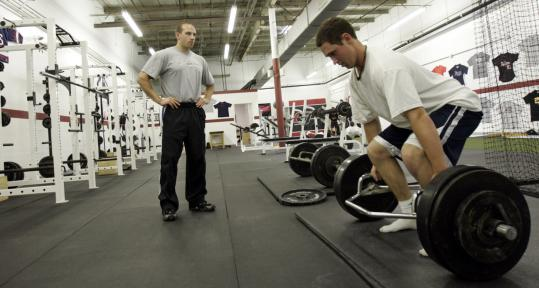 Eric Cressey oversees the training regimen for one of his clients at ...