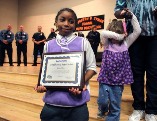 Richard Scott, a third-grade pupil at Tynan Elementary School in South Boston, displayed his certificate of appreciation during a ceremony by the Boston Police Department.