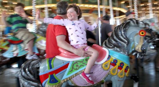 Liberty Rogers, 4, with her father Darby Rogers of Madison, Conn., was among the fans riding the Paragon Carousel on opening day.