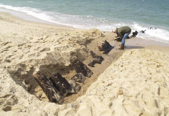 After erosion from recent storms, about a dozen of the HMS Somerset III's timbers were found poking through the wet sand at low tide in the national seashore in Provincetown.