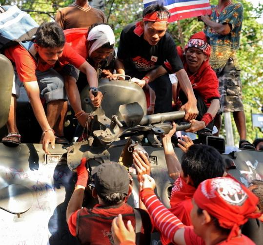 """Red Shirt'' protesters carried a weapon they dismantled from its mount on an armored government vehicle yesterday in Bangkok. The vehicle had been abandoned after clashes."