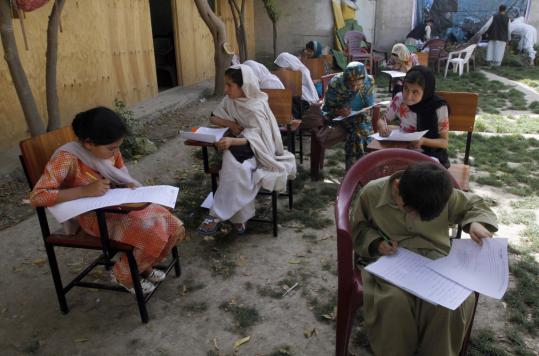 Students did their homework between classes at Afghan Canadian Center in Kandahar, Afghanistan yesterday. Thugs are increasingly harassing women who want an education.
