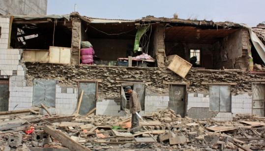 A strong earthquake injured more than 10,000 in the Tibetan region of China yesterday. A man stood in the rubble of a building in Jiegu township, Yushu County.