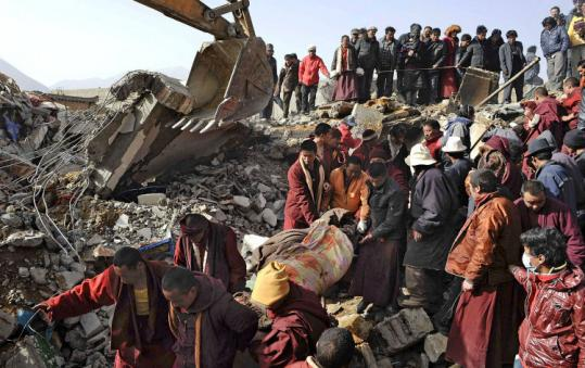 Rescuers, including Buddhist monks, carried an earthquake victim wrapped in a blanket in western China's Qinghai Province yesterday. China poured rescue crews and equipment into a mountainous Tibetan region after strong quakes killed hundreds of people and injured thousands.