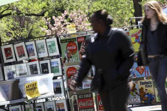 Pedestrians walked past artwork displayed by street vendors in Union Square recently. City officials say vendors selling their artwork have grown out of control.