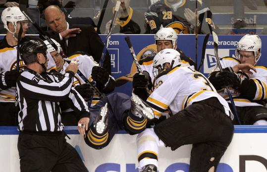 Boston captain Zdeno Chara delivers a message with a check that nearly lands the Sabres' Tyler Ennis in the Bruins' bench.