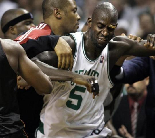 Kevin Garnett finds himself caught in the middle of a melee near the Heat bench late in Saturday night's Game 1.