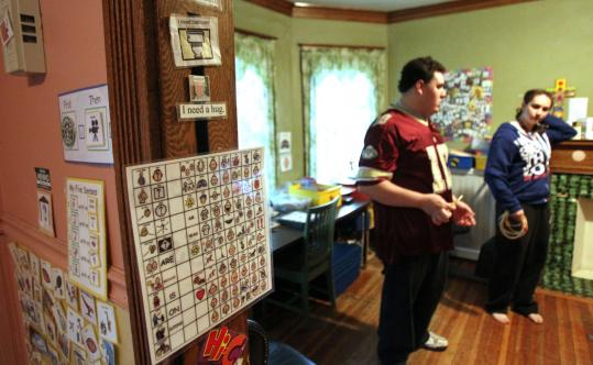Left: Marie Duggan has created a series of visual aids to communicate with her autistic 19-year-old son, Michael. Above: Michael and his sister Kate, 18, talk in the visual-aid-filled family home.