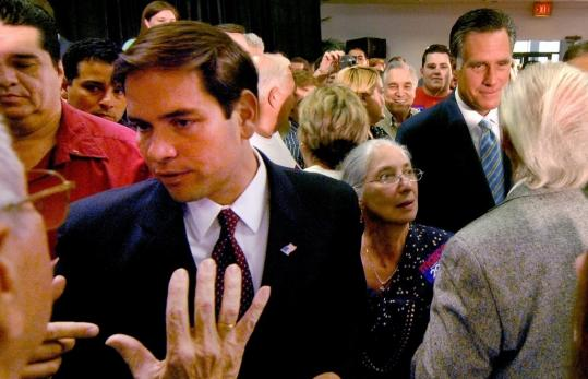 Marco Rubio, left, a US Senate candidate in Florida, greeted supporters with Mitt Romney yesterday in Tampa. Romney endorsed Rubio over Governor Charlie Crist of Florida.