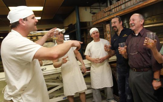 Stuart Witt (left), co-owner of Nashoba Brook Bakery in West Concord, toasts (and points to) Robert Kaiser (right), who came from France to install the bakery's new Fours Fringand oven.