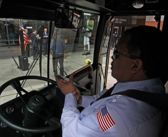 Bus driver Rafael Sanchez Jr. applauded a small launch ceremony at Back Bay Station yesterday from inside one of the T fleet's new hybrid buses.