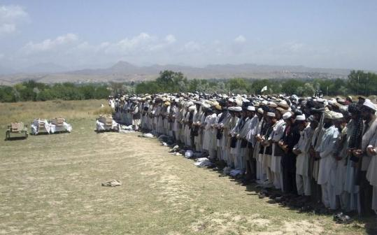 Afghans prayed  yesterday in Khost Province beside the coffins of four people killed  Monday night by NATO troops.