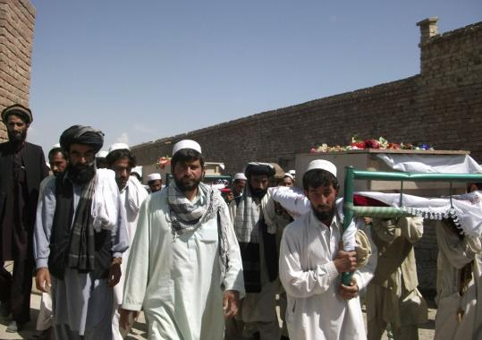 Afghans carried the coffins of four people killed when a driver  ignored warnings to stop near one of NATO's convoys on Monday.