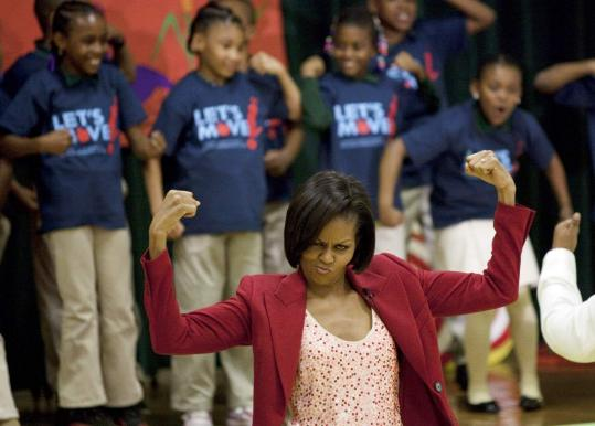 First lady Michelle Obama led by example as she flexed her muscles for students yesterday at the River Terrace Elementary School in Washington at an event to promote physical fitness.