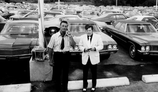 "Clair Auto Group, founded in 1964 by family patriarch James ""Ernie'' Clair (above, at right, in 1971), became one of New England's largest auto dealership chains. (On the left is Tony Nitti, general manager at the time.) Today, what is left of the business is run by sons Joseph Clair of Medfield and Michael Clair of Biddeford, Maine. They are accused in a lawsuit by their late brothers' wives of trying to freeze the widows out of the business."