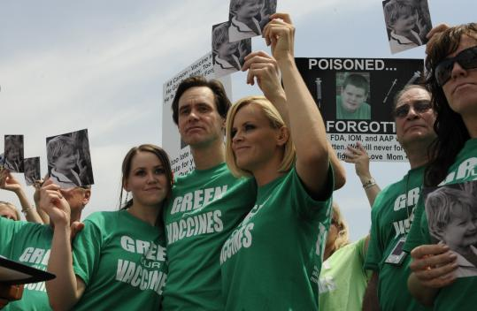 Actress Jenny McCarthy (center) holds a photo of her son Evan, who was diagnosed with autism, at a rally with actor Jim Carrey and his daughter Jenny (left).