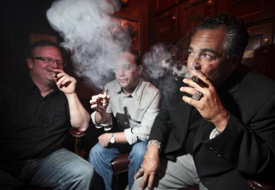 Jarrod McCormick and Mark Everett (from left) smoke with Stanza dei Sigari owner David Riccio at the North End cigar bar.