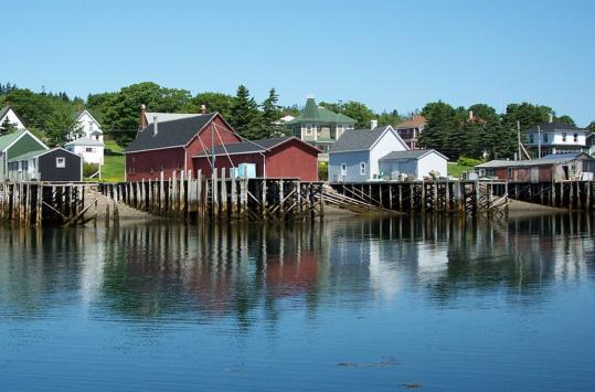 The docks at Brier Island's harbor are on stilts to accommodate the changing tides in the Gulf of Maine. Fishermen store their catch in the small warehouses. Tourists out on a whale watch contribute to the island's economy, but fishing is the mainstay.