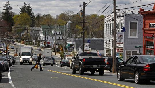 A pedestrian scurries across downtown Hopkinton's Main Street stretch of Route 135, which officials are working on to make more appealing.