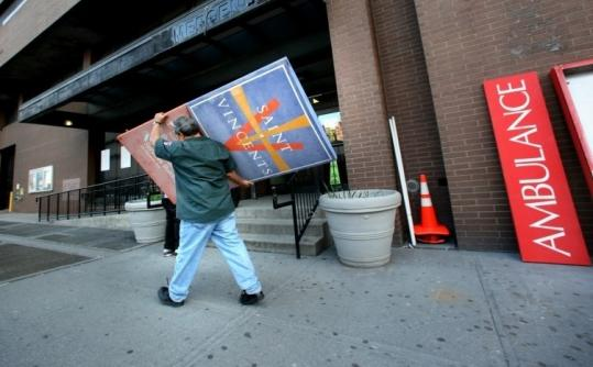A worker walked away with the nameplate for St. Vincent's Hospital in New York City after it shut permanently.
