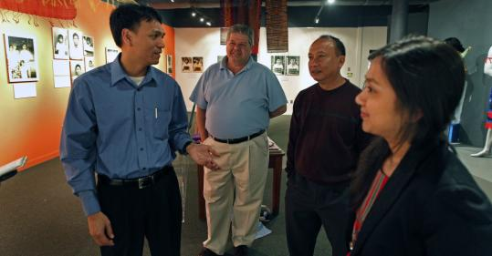 Sayon Soeun (left) talks with (left to right) Jim Coleman, Kowith Kret, and Sopheap Theam as they tour the exhibit.