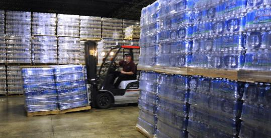 At CPF Co-Op in Ayer yesterday, a forklift moved pallets of Aquafina bottled water through the warehouse to the truck waiting to take them to communities hit by the boil-water order.
