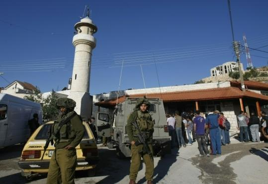 Palestinian civilians and Israeli soldiers gathered yesterday in front of a mosque that burned in a West Bank village.
