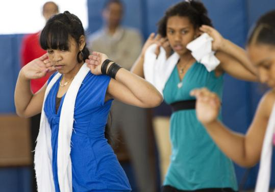 Young women performed a dance at St. Peter Teen Center in Dorchester after the new job funding was announced.
