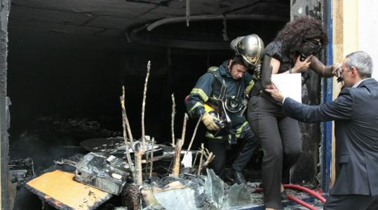 A woman was rescued from a bank in Athens that was torched by demonstrators yesterday (above) while others waited to be rescued. One fire official said protestors tried to prevent firefighters from reaching the building.