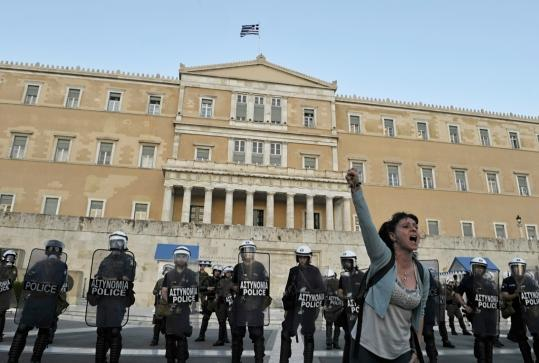 Tens of thousands of people demonstrated outside Parliament in Athens yesterday as lawmakers voted on an austerity package. Riot police used tear gas to push back the crowd.