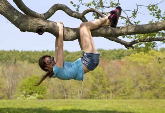 At Maudslay State Park in Newburyport, Kendra Stanton hangs from a tree.