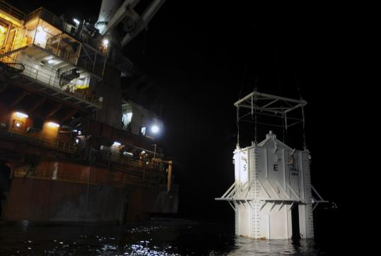 A four-story chamber, shown Thursday, was lowered to the bottom of the ruptured oil well in the Gulf of Mexico yesterday. The chamber has to settle for at least 12 hours before it can be hooked up in an attempt to capture most of the leaking oil.