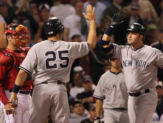 Mark Teixeira (25) greets Nick Swisher after Swisher got the Yankees going with a three-run homer in the fourth.