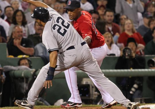 The Yankees' Randy Winn keeps his foot on the bag, depriving third baseman Adrian Beltre of a putout in the sixth inning.