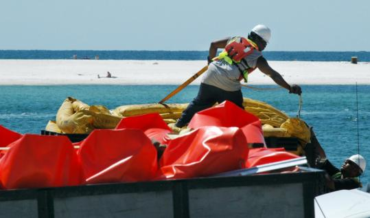 Workers handled booms in a parking lot in Orange Beach, Ala., as people relaxed on the beach across Perdido Pass yesterday. The state is using booms to stop oil from entering the pass.