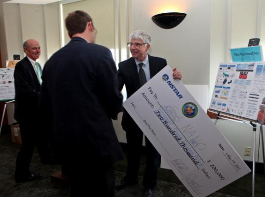 Melburne LeMieux, cofounder of C3Nano, accepted first prize yesterday from NStar chief Tom May in an MIT competition.