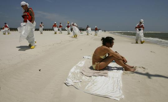 A woman relaxed on the beach in Dauphin Island, Ala., earlier in the week while workers in protective suits searched for tar balls from the huge April 20 oil spill in the Gulf of Mexico.