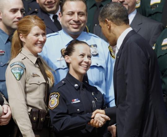 President Obama greeted Sergeant Kimberly Munley (center) of the Fort Hood Police Department after presenting her and other officers with awards at the White House yesterday.