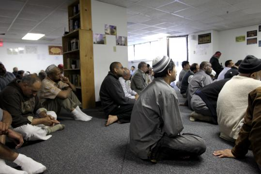 "Men at the Allston-Brighton Islamic Center listened to Hassan Mohamed preach at services yesterday. ""Islam means peace,'' the imam said."