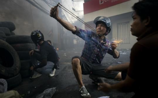 An antigovernment protester fired a firecracker-loaded slingshot at Thai military forces during street clashes in Bangkok yesterday as violence in the central part of the city escalated.