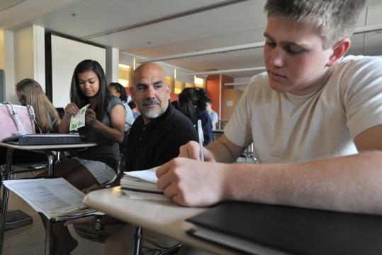 Northern Essex Community College professor Xavier Pelaez (center) checks work by Amesbury High students Lyanh Harding-Lu and Troy Wise.