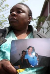"Krystal Sanders, 30, held a photo of her slain niece, Aiyana Jones, 7. Officers had entered the home with guns drawn and had ""some level of physical contact'' with a woman inside."