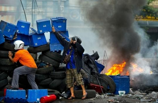 Antigovernment protesters shot slingshots to taunt the military from behind tire barriers in Bangkok yesterday.
